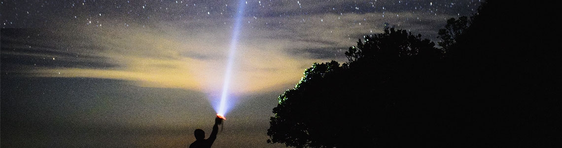 A man holding a flashlight against the night sky. Very high impact.
